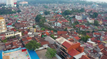 резиденция : BANDUNG, Indonesia - July 03, 2019: Aerial scenery of crowded residential houses in Bandung city, West Java, Indonesia. Shot in 4k resolution from a drone flying forwards Стоковые видеозаписи