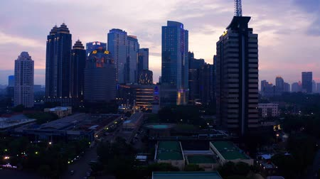 flying upwards : JAKARTA, Indonesia - July 03, 2019: Aerial view of silhouette of modern skyscrapers in financial district at sunset time. Shot in 4k resolution from a drone flying upwards