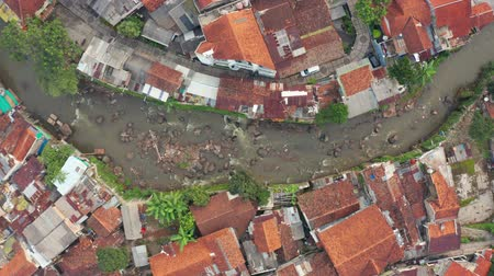 flying upwards : BANDUNG, Indonesia - July 03, 2019: Top down view of crowded residential houses on the riverside in Bandung city, West Java, Indonesia. Shot in 4k resolution from a drone flying upwards