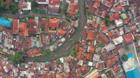 flying upwards : BANDUNG, Indonesia - July 03, 2019: Top down view of a river with crowded residential houses on the riverside in Bandung city, West Java, Indonesia. Shot in 4k resolution from a drone flying upwards Stock Footage