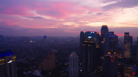 central business district : JAKARTA, Indonesia - July 03, 2019: Beautiful aerial view of financial district with silhouette of skyscrapers at twilight time. Shot in 4k resolution from a drone flying from right to left