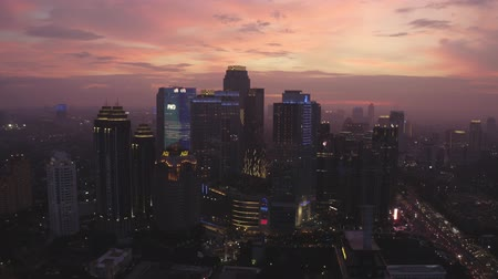flying upwards : JAKARTA, Indonesia - July 03, 2019: Beautiful aerial scenery of silhouette of modern skyscrapers in business district at twilight time. Shot in 4k resolution from a drone flying upwards Stock Footage