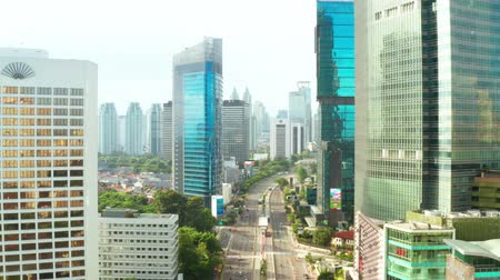 sudirman : JAKARTA, Indonesia - July 03, 2019: Aerial landscape of Sudirman street with skyscrapers background around Hotel Indonesia roundabout. Shot in 4k resolution from a drone flying down