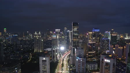 szemléltető : JAKARTA, Indonesia - July 08, 2019: Beautiful aerial view of long traffic jam on highway between modern skyscrapers at night. Shot in 4k resolution