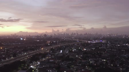 yoğunluk : JAKARTA, Indonesia - July 09, 2019: Beautiful aerial view of Jakarta city with dense residential houses at dusk time. Shot in 4k resolution from a drone flying from right to left Stok Video