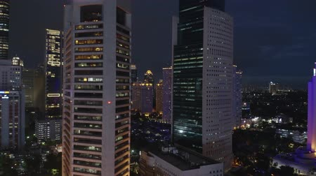 szemléltető : JAKARTA, Indonesia - July 09, 2019: Aerial landscape of modern office building exterior with glass windows at night in business district. Shot in 4k resolution from a drone flying upwards