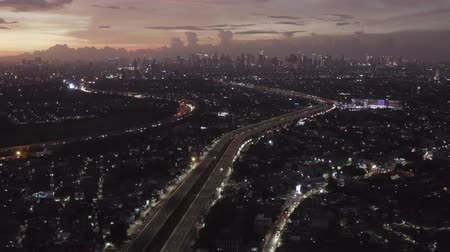 yoğunluk : JAKARTA, Indonesia - July 09, 2019: Beautiful aerial landscape of Becakayu toll road between dense residential houses at dusk. Shot in 4k resolution from a drone flying backwards