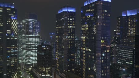 metropolitní : JAKARTA, Indonesia - July 09, 2019: Aerial view of silhouette of modern office buildings and apartment in central business district at night. Shot in 4k resolution from a drone flying forwards Dostupné videozáznamy