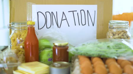 donate : Donation concept. Cardboard box and foods for donation. Shot in 4k resolution