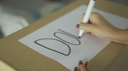 usado : Closeup of woman hands writing a Donate text on the cardboard box. Shot in 4k resolution