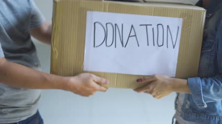 humanismo : Donation concept. Man giving a donation cardboard box on a woman. Shot in 4k resolution