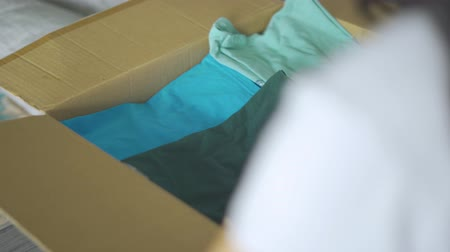 endowment : Donation concept. Young woman collecting used clothes in a cardboard box for donating. Shot in 4k resolution Stock Footage