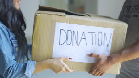 未使用 : Donation concept. Young woman giving a donation cardboard box on a man. Shot in 4k resolution