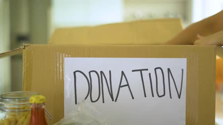 endowment : Donation concept. Woman hand collects foodstuff for donation into the cardboard box. Shot in 4k resolution Stock Footage
