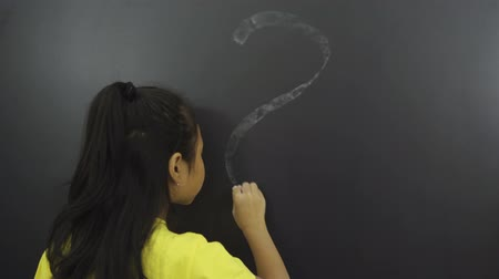 verwarring : Back to School Concept. Female elementary school student drawing a question mark on the chalkboard in the classroom. Shot in 4k resolution
