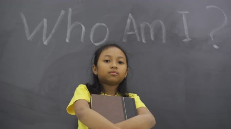 ders kitabı : Female elementary school student standing in the class while holding a book with text of Who Am I? Stok Video