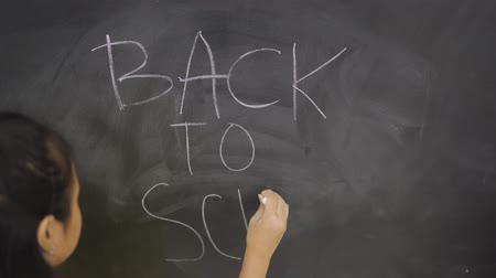 persons : Female elementary school student writing a Back to School text on the chalkboard in the classroom. Shot in 4k resolution