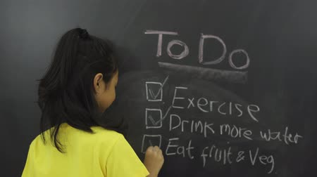 mais : Happy female elementary school student writing to do list on the blackboard in the classroom. Shot in 4k resolution