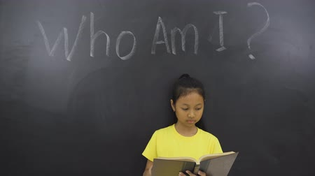 şahsiyet : Female elementary student reading a book in the class with text of Who Am I?