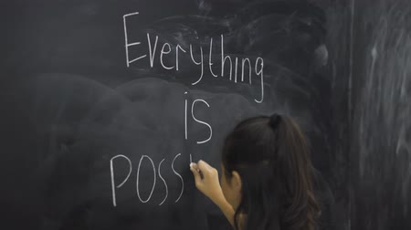 everything : Female elementary school student writing text of Everything is Possible on the chalkboard in the classroom. Shot in 4k resolution Stock Footage