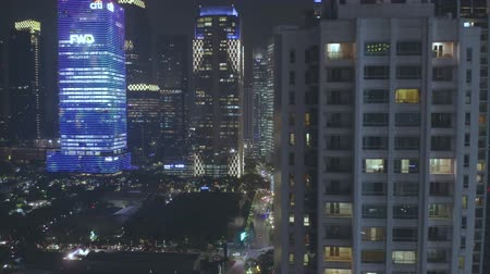 apartamentos : JAKARTA, Indonesia - July 15, 2019: Aerial view of apartment buildings and skyscrapers with night lights in business center. Shot in 4k resolution from a drone flying from right to left Stock Footage