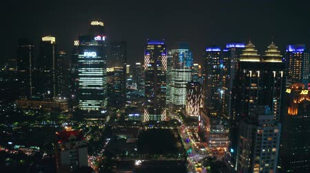 distrito financeiro : JAKARTA, Indonesia - July 15, 2019: Aerial view of modern office buildings tower and beautiful night lights in business district. Shot in 4k resolution from a drone flying forwards