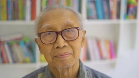 книжный шкаф : Portrait of elderly man with wrinkled face and wearing glasses, looking at the camera in the library room. Shot in 4k resolution