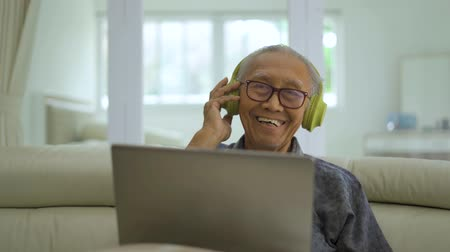 しわの寄った : Happy senior man listening music with a laptop computer and headphones while sitting on the sofa in living room at home. Shot in 4k resolution