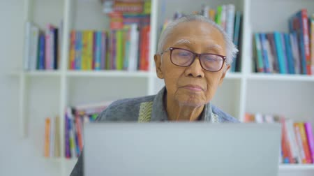 книжный шкаф : Senior man using a laptop computer while wearing glasses in the library. Shot in 4k resolution Стоковые видеозаписи