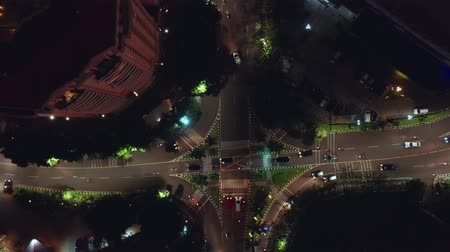 пересечение : JAKARTA, Indonesia - July 15, 2019: Top down view of a road intersection at night in business center. Shot in 4k resolution from a drone flying upwards