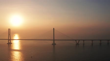 toll : Exotic aerial landscape of sunrise with silhouette of Suramadu bridge and sunlight reflection on Madura strait. Shot in 4k resolution from a drone flying from right to left