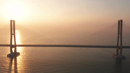 madura : Exotic aerial scenery of Suramadu bridge on the Madura strait with golden sunlight reflection at sunrise. Shot in 4k resolution from a drone flying forwards Stock Footage