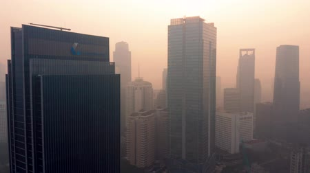 flying upwards : JAKARTA, Indonesia - July 17, 2019: Aerial view of air pollution and modern skyscrapers in financial district on the morning. Shot in 4k resolution from a drone flying upwards