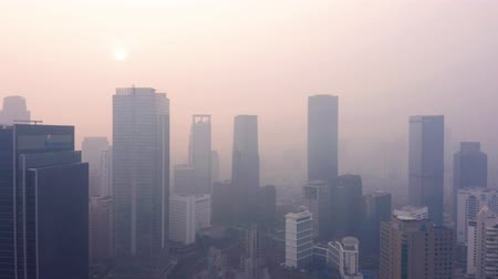 central business district : JAKARTA, Indonesia - July 17, 2019: Aerial view of air pollution haze and silhouette of skyscrapers in business center. Shot in 4k resolution from a drone flying forwards