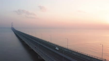 madura : Beautiful aerial view of Suramadu bridge at sunrise time on Madura strait from Surabaya city to Madura island, East Java, Indonesia. Shot in 4k resolution from a drone flying from left to right