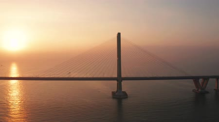 madura : Exotic aerial view of silhouette of Suramadu bridge and sunlight reflection on Madura strait at sunrise in Surabaya, East Java, Indonesia. Shot in 4k resolution from a drone flying from right to left