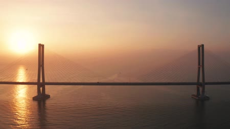 madura : Exotic aerial view of Madura strait and Suramadu bridge at sunrise with golden sunlight reflection. Shot in 4k resolution from a drone flying forwards Stock Footage
