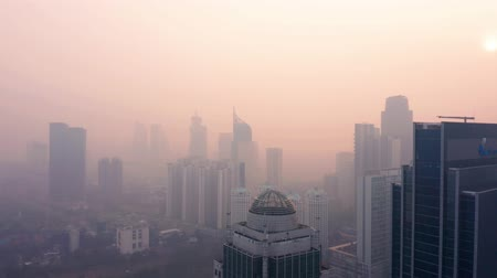 forwards : JAKARTA, Indonesia - July 17, 2019: Aerial landscape of air pollution in business center with silhouette of modern skyscrapers on the morning. Shot in 4k resolution from a drone flying forwards