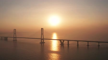 madura : Beautiful aerial view of sunrise time with golden sunlight reflection and silhouette of Suramadu bridge on Madura strait. Shot in 4k resolution from a drone flying from right to left