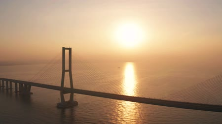 madura : Exotic aerial view of Suramadu bridge at sunrise with sunlight reflection on the Madura strait in Surabaya, East Java, Indonesia. Shot in 4k resolution from a drone flying from left to right