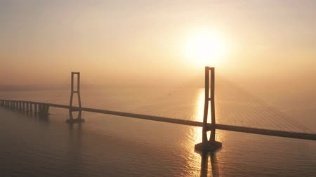 madura : Exotic aerial landscape of Suramadu bridge at sunrise on Madura strait with sunlight reflection in Surabaya, East Java, Indonesia. Shot in 4k resolution from a drone flying from left to right