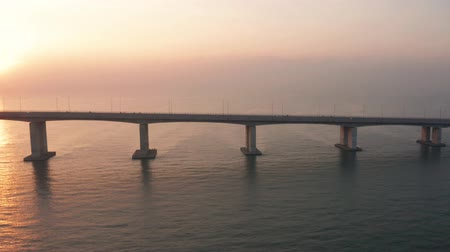 madura : Beautiful aerial view of Suramadu bridge on Madura strait with sunlight reflection at sunrise in Surabaya, East Java, Indonesia. Shot in 4k resolution from a drone flying from right to left Stock Footage