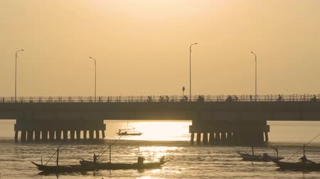 madura : Beautiful view of Suramadu bridge with fisherman boats and sunlight reflection on misty morning in Surabaya city to Madura island at East Java, Indonesia. Shot in 4k resolution