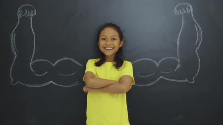 orgulho : Pretty female elementary school student standing in the classroom with strong hands or chalk muscles on the blackboard. Shot in 4k resolution