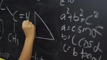 vzorec : Unknown hand of female elementary school student writing triangle formula on the blackboard in the classroom at school. Shot in 4k resolution