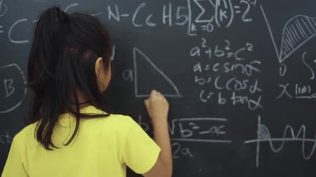 elmélet : Pretty female elementary school student writing triangle formula on the chalkboard and smiling in the classroom at school. Shot in 4k resolution