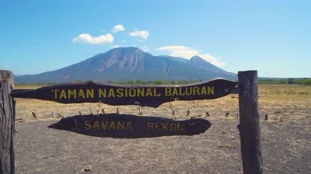 uithangbord : EAST JAVA, Indonesia - July 23, 2019: Signboard of Baluran National Park with beautiful Bekol Savanna and Mount Baluran background. Shot in 4k resolution