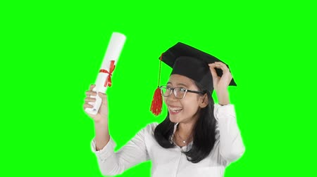 promoce : Slow motion of happy Asian woman celebrating her graduation while holding a diploma and wearing a graduation cap in the studio with green screen background