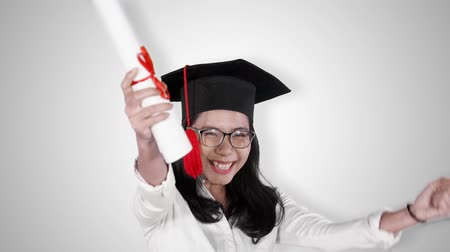 promoce : Slow motion of attractive woman celebrating her graduation and success while wearing a graduation cap and holding a diploma. Isolated on white background