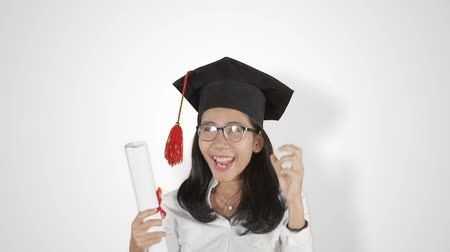promoce : Slow motion of cheerful young woman celebrating her graduation while wearing a graduation hat and holding a diploma. Isolated on white background Dostupné videozáznamy